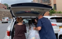 Volunteers unload a car with supplies