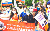 "Participants of the Tu Cuentas Immigration March and Census Fair, holding several flags and a red banner with white text that reads ""New York State Senator Julia Salazar Senate District 18. The Senator is in the foreground with a megaphone."