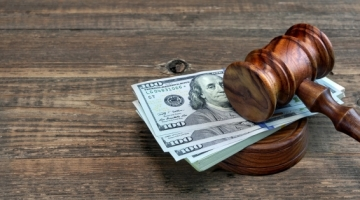 A gavel on a pile of one-hundred dollar bills.