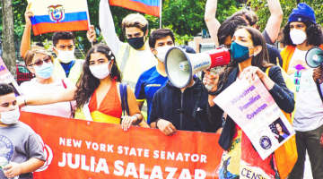 """Participants of the Tu Cuentas Immigration March and Census Fair, holding several flags and a red banner with white text that reads """"New York State Senator Julia Salazar Senate District 18. The Senator is in the foreground with a megaphone."""