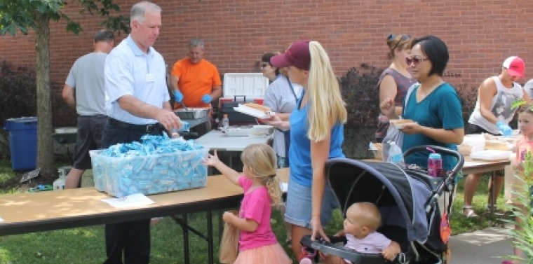 Senator Ranzenhofer hands out rice krispies treats during a picnic at the Amherst Library.